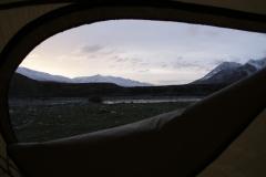 Blick aus dem Zelt auf die verschneiten Berge.